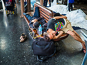 11 APRIL 2018 - BANGKOK, THAILAND:  Men sleep while they wait for a train at Hua Lamphong train station in Bangkok on the first day of the Songkran travel period. Songkran is the traditional Thai New Year and is one of the busiest travel periods of the year as Thais leave the capital and go back to their home provinces or resorts in tourist areas. Trains and busses are typically jammed the day before the three day Songkran holiday starts. The government has extended the official holiday period through Monday, 16 April because one day of the Songkran holiday fell on the weekend, giving many workers a five day holiday.   PHOTO BY JACK KURTZ