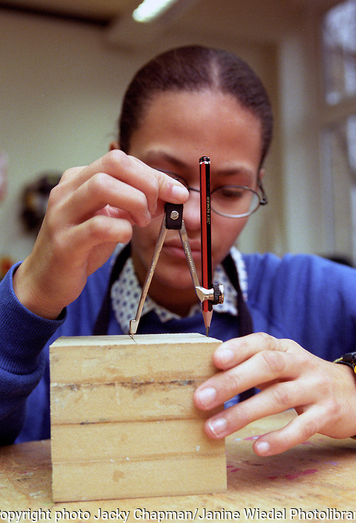 Young student in constructing a model  in wood lesson at College of design and technology