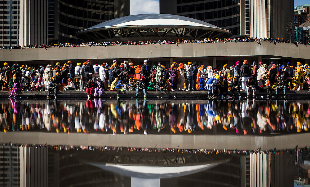 Toronto, Ontario - April 26, 2015 --  Sikhs Khalsa Day Parade  -- People are reflected in Nathan Philips Square during the Sikhs Khalsa Day Parade in Toronto, Sunday April 26, 2015.   (Mark Blinch for the Globe and Mail)