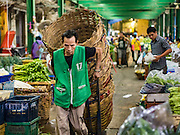 """21 DECEMBER 2015 - BANGKOK, THAILAND:  Porters in Pak Khlong Talat, also called the Flower Market. The market has been a Bangkok landmark for more than 50 years and is the largest wholesale flower market in Bangkok. A recent renovation resulted in many stalls being closed to make room for chain restaurants to attract tourists. Now Bangkok city officials are threatening to evict sidewalk vendors who line the outside of the market. Evicting the sidewalk vendors is a part of a citywide effort to """"clean up"""" Bangkok.      PHOTO BY JACK KURTZ"""