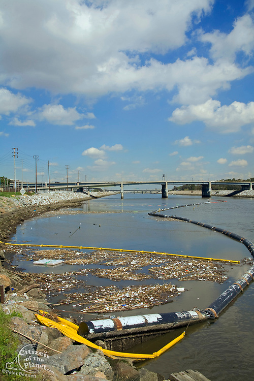 The Garbage boom on the Los Angeles River in Long Beach was built in 2001. Urban runoff carries an assortment of trash and debris from catch basins where a network of pipes and open channels create a pathway to the Ocean. The man made debris can include plastic bags and bottles, Styrofoam cups, cans, tires, and household furniture. After the first major storm of the season, the boom may collect over 50,000 pounds of trash.
