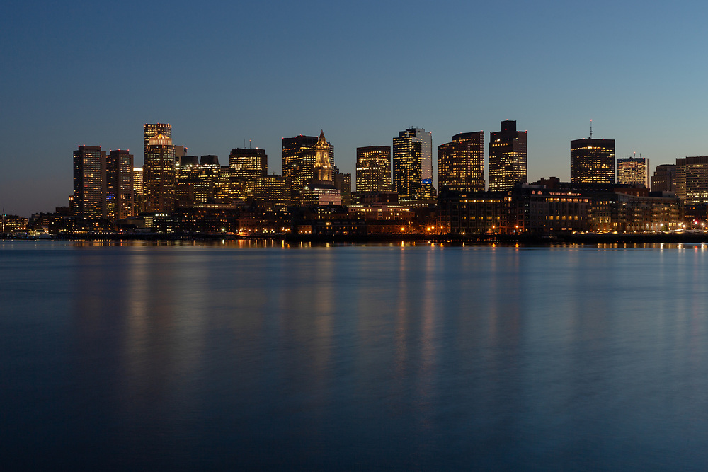 The glowing Boston skyline seen from across the harbor along the East Boston piers.