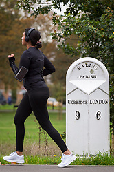 © Licensed to London News Pictures. 17/10/2020. LONDON, UK. A woman runs past a distance marker in Ealing, west London.  The Office for National Statistics (ONS) has reported that the confirmed coronavirus cases in the capital exceed 67,000, with Ealing having the highest Covid-19 rate amongst London Boroughs at 144 cases per 100.  Following the UK Government's announcement, the capital has today moved from Tier 1 to Tier 2, meaning a ban on indoor social mixing between households in the capital.  Photo credit: Stephen Chung/LNP