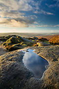 Colourful skies reflect in a pool of water on grtistone rocks at Higger Tor in Derbyshire's Peak District. Dawn light in the English countryside. October 2014.