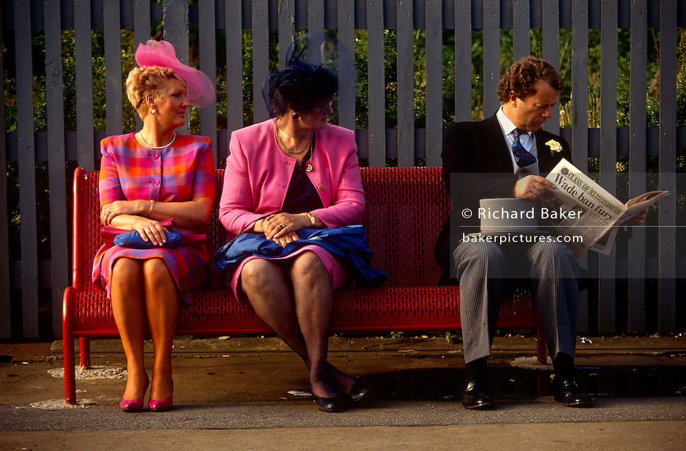 Two women dressed in bright pink sit on a station bench en-route to Ascot racecourse on Ladies Day at Royal Ascot racing week. A man with top hat and tails sits reading a newspaper with a Wimbledon tennis news headline on the back page, Royal Ascot is held every June and is one of the main dates on the sporting calendar and English social season. Over 300,000 people make the annual visit to Berkshire during Royal Ascot week, making this Europe's best-attended race meeting. There are sixteen group races on offer, with at least one Group One event on each of the five days. The Gold Cup is on Ladies' Day on the Thursday. There is over £3 million of prize money on offer.