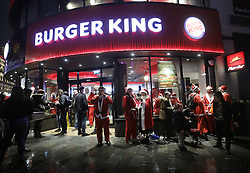 Revellers outside Burger King in Leicester Square, London, taking part in the Santacon Christmas parade.