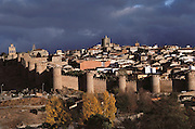 The walled city of Avila, Spain under storm clouds.