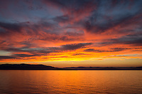 A vibrant sunset is reflected on Flathead Lake, Montana.