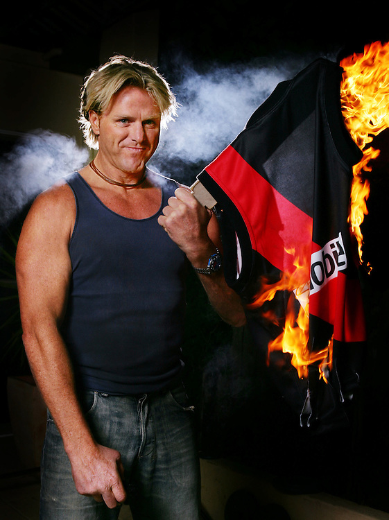 """Hawthorn Hawks legend Centre Half Forward Dermott Brereton loved to hate the Essendon Bombers so he jumped at the chance when I asked him if he'd like to burn a Bombers jumper for AFL Rivalry Round.<br /> I met him at his house and he got out the petrol container from the shed. For good effect he put on his Bonds singlet, got out the lighter and """"boof"""" the jumper exploded into flames.<br /> Years later I was speaking to Ian Robson, the Hawks CEO at that time of the photo being published, and he said he had to write a letter of apology to the Bombers as Derm was actually on the board of directors with the Hawks. Whoops, sorry Robbo! (Copyright Michael Dodge/Herald Sun)"""