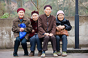 Elderly Chinese women sit together on a bench in Chongqing, China