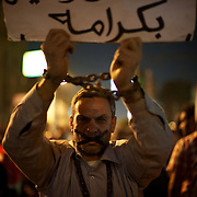 December 11, 2012 - Cairo, Egypt: A protestor displays a poster outside the presidential place in Cairo, where tens of thousands gathered to voice their anger at the planned constitution, which will be put to a referendum next Saturday...The Egyptian army has reportedly called talks between President Mohamed Morsi and the opposition to end violent protests against a draft constitution...Sporadic clashes between supporters and opponents of president Mohamed Morsi, erupted in the past week over his assumption of extraordinary powers and the scheduling of the referendum. (Paulo Nunes dos Santos/Polaris)