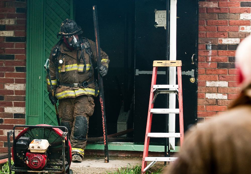 Matt Dixon   The Flint Journal..A firefighters removes a smoldering board from Carpenter Apartments at the intersection of Carpenter Road and Orangle Lane in Flint Saturday afternoon.