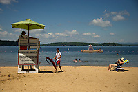 Lifeguards Seth Valpey and Beck McLean rotate shifts along Gilford Beach on Friday morning.  (Karen Bobotas/for the Laconia Daily Sun)
