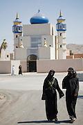 Women walk on the street in a fabricated Iraqi village of Medina Wasl, at Camp Irwin,  California.