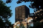 A resident in a low rise flat looks at the burnt shell of Grenfell Tower on the 16th June 2017 in North Kensington, London, United Kingdom. The Grenfell Tower fire occurred on 14th June 2017 at the 24-storey block of public housing flats in North Kensington, West London. It caused at least 80 deaths and over 70 injuries, yet the actual numbers have yet to be confirmed