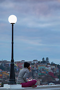 Woman sitting on wall under street lamp at dawn, Valparasio, Chile