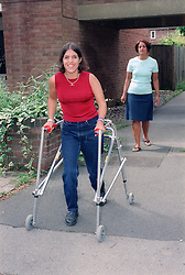 Mother watching daughter with Cerebral Palsy using frame to walk along pavement,
