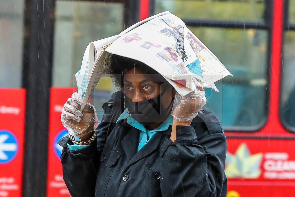 © Licensed to London News Pictures. 02/10/2020. London, UK. A woman shelters from rain underneath a newspaper in north London as Storm Alex arrives from Europe. The Met Office forecasts heavy rain and windy weather for the next few days in the capital, caused by Storm Alex. Photo credit: Dinendra Haria/LNP