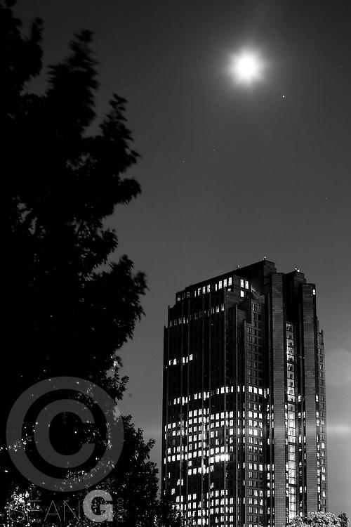 skyscraper stands underneath a moonrise in Dallas, Texas