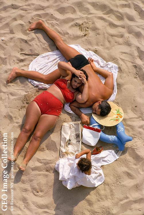 A family resting and sunbathing on a sandy beach.