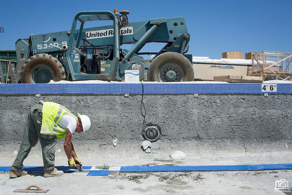 Enes Vukovic of Bosnia brushes lays lane marker tiles in the warming pool at Milpitas High School in Milpitas, California, on July 18, 2014. (Stan Olszewski/SOSKIphoto)