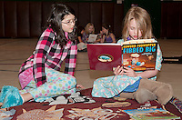 """Addy Dinsmoor and Gillian Rollins get """"comfy"""" with their pj's and a book at Holy Trinity Catholic School Tuesday evening after a visit to the Book Fair with milk and cookies to follow.   (Karen Bobotas/for the Laconia Daily Sun)"""