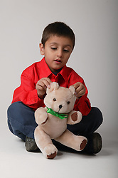 Young boy sitting on the floor and playing with a teddy bear,