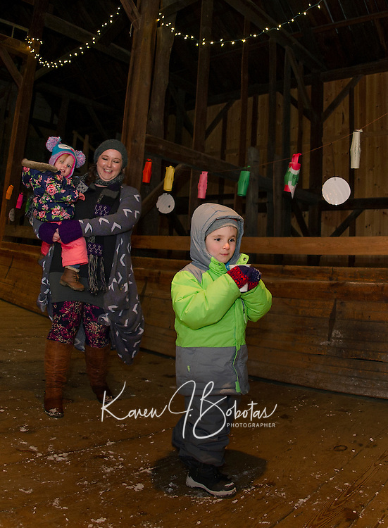 Penelope, Audrey and Gabriel Smith enjoy hot chocolate in the barn at Prescott Farm during the Lantern Festival held Saturday evening.  (Karen Bobotas/for the Laconia Daily Sun)