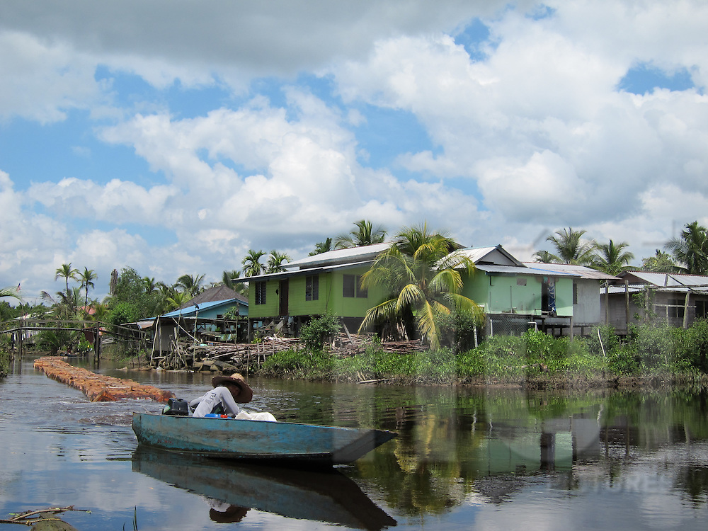 Woman boating along river surrounded by stilt houses, Malaysia, Southeast Asia