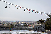 21st century shoes hang from cables above Stalinist-era architecture in Letna Park (Letenske Sady), on 18th March, 2018, in Prague, the Czech Republic. Up until it was destroyed by Soviet leader Nikita Kruschev, the largest statue to Stalin in the entire Eastern Bloc was located here. It is now a favourite place skateboard park, dog walkers and families. Like Rome, Prague is built on seven hills.