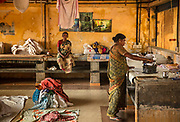 """Ironing clothes in the Dhobi Khana laundry collective, run by a group of Tamil families, on 28th February 2018 in Kochi, Kerala, India. Kochi's historic Dhobi Khana, nestled among quaint Fort Kochi streets, is run by the Vannar community from Tamil Nadu. The Dhobi Khana laundry collective comprises around 50 families who offer their services to hospitals, households, hostels, hotels, government organisations, and even a few cruise ships. """"Washing booths and water pools are allotted to each family. We wash clothes by beating them directly and repeatedly on stone slabs."""
