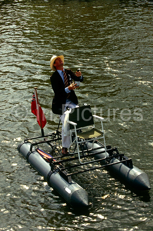 Messing about on a pedal water craft, a member of a local rowing club looks up to see where the cork to his opened champagne bottle will land on the River Thames during a particularly hot afternoon at the Henley Royal Regatta boat races, England. During this annual festival of high-society, serious rowing and general clowning around on the rural Thames. In 1829 a boat race challenge was held between teams representing the universities of Oxford and Cambridge. The venue chosen was a straight stretch of the Thames at the small town of Henley-on-Thames. Now held July and is one of the main dates on the sporting calendar and social season for the wealthy upper-classes.