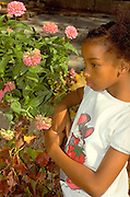 Thoughtful girl age 9 surrounded by a blooming flower garden.  St Paul Minnesota USA