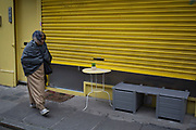 Tiny set of stick on eyes peers out from yellow shutters at passers by near to Brick Lane, in the East End of London, UK. A miniature piece of street art, these eyes appear to be watching as people pass this closed cafe.