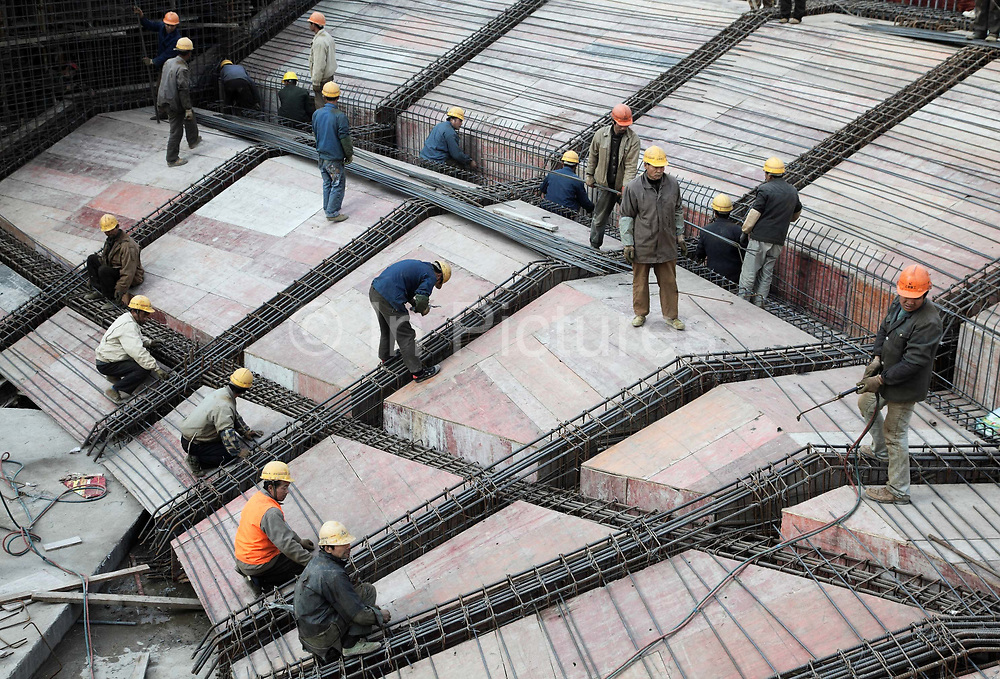 Workers build the foundation for a bowl-like plaza at a new shopping center in Shanghai, China on 23 November 2009.