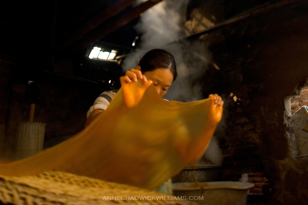 A woman stretches noodles in her noodle making shop in northern Vietnam.