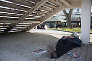 Man having a sleep under a stairway leading up the the Royal Festival Hall. The South Bank is a significant arts and entertainment district, and home to an endless list of activities for Londoners, visitors and tourists alike.