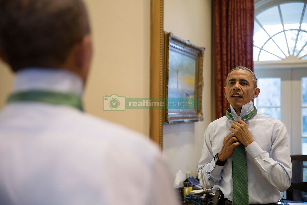 President Barack Obama puts on a green tie in observance of St. Patrick's Day, in the Outer Oval Office, March 17, 2015. (Official White House Photo by Pete Souza)<br /> <br /> This official White House photograph is being made available only for publication by news organizations and/or for personal use printing by the subject(s) of the photograph. The photograph may not be manipulated in any way and may not be used in commercial or political materials, advertisements, emails, products, promotions that in any way suggests approval or endorsement of the President, the First Family, or the White House.