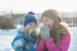 Children eating green apple on snow field