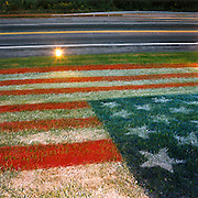 """Patriotic Americana - After 9/11. An aerosol American flag sprayed on a grassy knoll. In the week after the September 11th attacks, America sought to express their anger and patriotic unity. Evidence of a resilient nation was found on many roadsides. Here, a local garage owner has aerosol-sprayed the Stars and Stripes onto a grassy verge on Highway 422 in Sinking Spring, Pennsylvania..""""These Colours Don't Run."""" - From a New York City T-shirt..."""
