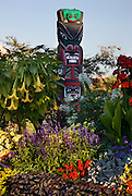 Flowers and a totem pole along the  Inner Harbour, Victoria, Vancouver Island, British Columbia, Canada.