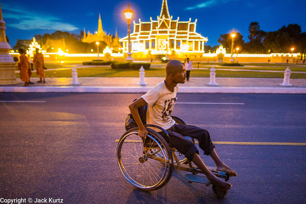 02 FEBRUARY 2013 - PHNOM PENH, CAMBODIA:   A man in a wheelchair rolls down Sisowath Quay, Phnom Penh's riverfront boulevard which is normally choked with cars and motorcycles. The Royal Palace is lit up in the background. Much of Phnom Penh has been shut down to honor former King Norodom Sihanouk, who ruled Cambodia from independence in 1953 until he was overthrown by a military coup in 1970. Only bars, restaurants and hotels that cater to foreign tourists are supposed to be open. The only music being played publicly is classical Khmer music. Sihanouk died in Beijing, China, in October 2012 and will be cremated during a state funeral royal ceremony on Monday, Feb. 4.   PHOTO BY JACK KURTZ