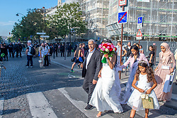 © Licensed to London News Pictures. 21/09/2019. Paris, France. Against a backdrop of riot police a new bride leaves a wedding ceremony as nearby protesters clash with police at a climate change demonstration in Paris. Photo credit: Peter Manning/LNP