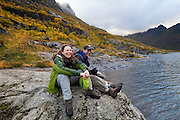 Liana and Parmenter Welty sit on the shore of Agvatnet Lake above Å, Lofoten Islands, Norway.