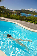 Nude woman swimming underwater in pool with St. Jean Bay, St. Barthelemy in distance