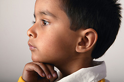 Profile of a young boy with hand under chin,
