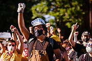 28 JULY 2020 - DES MOINES, IOWA: Black Lives Matter protesters stand in the middle of Grand Ave and yell towards the Governor's Mansion in Des Moines. It was not clear if they could be heard in the mansion, and no one came out to talk to them. About 150 supporters of Black Lives Matter marched from downtown to Des Moines to the Governor's Mansion. They were demanding that Iowa Governor Kim Reynolds restore the voting rights for felons who have completed their sentence. In June, Reynolds met with representatives of Black Lives Matter and promised to sign an executive order to restore voting rights, but she hasn't said anything more about it in six weeks. Iowa is now the only state in the US that permanently strips felons of their voting rights. That means 60,000 people in Iowa can't vote.    PHOTO BY JACK KURTZ