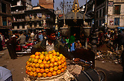A man sells fresh oranges from his bicycle in chaotic street in Kathmandu, Nepal. In the heart of the Nepali capital, the busy streets are popular with produce sellers and shoppers as wellas tourists to see the genuine sprawl of Kathmandu, a destination for travellers from around the world. Amid the dark and dirty background, the oranges become a bright addition to this urban landscape. Oranges are grown in places such as Nayagaun Gulmi. Kathmandu is the capital and largest urban agglomerate of Nepal. Its 2011 census shows it has a population of more than 2.5 million inhabitants.