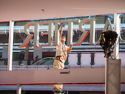 """27 MARCH 2015 - BANGKOK, THAILAND: A worker cleans the front window for """"EmQuartier,"""" a new mall in Bangkok. """"EmQuartier"""" is across Sukhumvit Rd from Emporium. Both malls have the same corporate owner, The Mall Group, which reportedly spent 20Billion Thai Baht (about $600 million US) on the new mall and renovating the existing Emporium. EmQuartier and Emporium have about 450,000 square meters of retail, several hotels, numerous restaurants, movie theaters and the largest man made waterfall in Southeast Asia. EmQuartier celebrated its grand opening Friday, March 27.    PHOTO BY JACK KURTZ"""