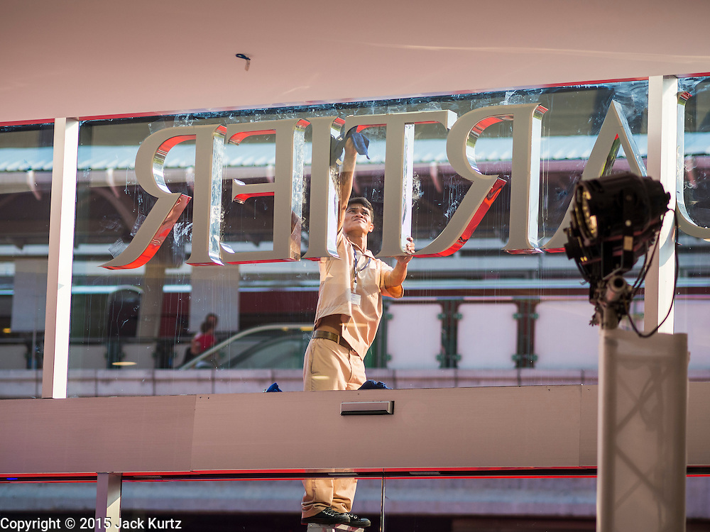 "27 MARCH 2015 - BANGKOK, THAILAND: A worker cleans the front window for ""EmQuartier,"" a new mall in Bangkok. ""EmQuartier"" is across Sukhumvit Rd from Emporium. Both malls have the same corporate owner, The Mall Group, which reportedly spent 20Billion Thai Baht (about $600 million US) on the new mall and renovating the existing Emporium. EmQuartier and Emporium have about 450,000 square meters of retail, several hotels, numerous restaurants, movie theaters and the largest man made waterfall in Southeast Asia. EmQuartier celebrated its grand opening Friday, March 27.    PHOTO BY JACK KURTZ"